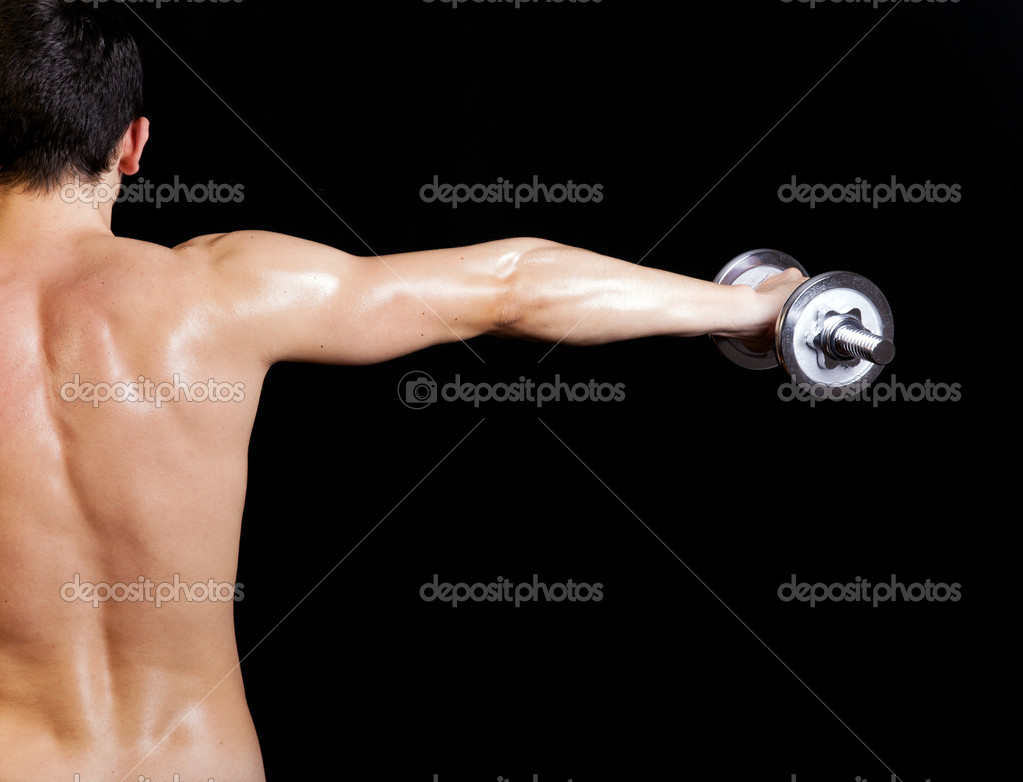 Back view of a young male doing exercise with dumbbells against dark background — Stock Photo #13647880