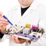 Computer Engineer examining, repairing a electronic circuit — Stock Photo #13650261