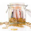 Money jar with savings, isolated on white - Stok fotoğraf