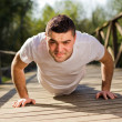 Стоковое фото: Young man exercising at the park