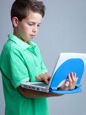 Boy with laptop on grey background — Stock Photo