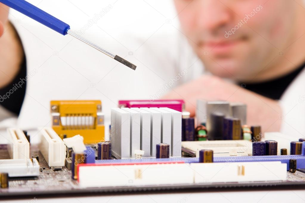 Computer Engineer examining, repairing a electronic circuit, isolated over white background  Stock Photo #13650284