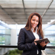 Smiling business woman using a tablet PC at the office — Stock Photo