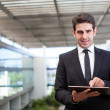 Smiling young businessman using his digital tablet at the office — Stock Photo