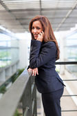 Smiling young business woman talking on cell phone at the office — Stock Photo