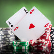 Poker chips and playing cards on green background — Stock Photo #15873707