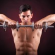 Image of a muscular young man lifting weights on black backgroun — Stock Photo