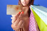 Hermosa mujer compra con una tarjeta de crédito en fondo azul — Foto de Stock