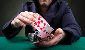 Poker player throwing cards on black background — Stock Photo