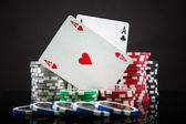 Poker chips and playing cards on black background — Stock Photo