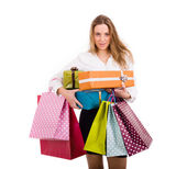 Shopaholic young woman holding gifts and shooping bags on white — Stock Photo