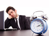 Tired young businessman sleeping next laptop on white background — Stock Photo