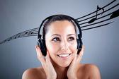 Linda menina com fones de ouvido e notas musicais voando na cinza — Fotografia Stock