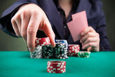 Poker player on black background — Stock Photo