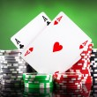 Poker chips and playing cards on green background — Stock Photo #17977425