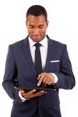 Thoughtful african american young businessman with tablet comput — Stock Photo
