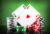 Poker chips and playing cards on green background — Stock Photo