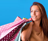 Beautiful young woman holding shopping bags, isolated on blue st — Stock Photo