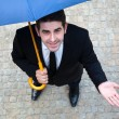 Young business man with umbrella checking if it's raining — Stok fotoğraf