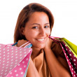 Portrait of a beautiful woman holding shopping bags against whit — Stock Photo