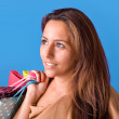 Portrait of a beautiful young woman holding shopping bags over b — Stock Photo
