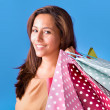 Stock Photo: Portrait of a beautiful young woman holding shopping bags over b