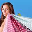 Portrait of a beautiful young woman holding shopping bags over b — Stock Photo #19934919
