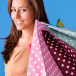 Stock Photo: Beautiful young womholding shopping bags, isolated on blue st