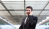 Successful young business man talking on cell phone at modern of — Stock Photo
