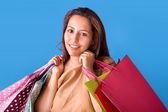 Schöne junge frau shopping taschen, isoliert auf blau st — Stockfoto