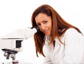 Portrait of female scientist working with a microscope, isolated — Stock Photo