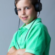 Portrait of a smiling boy listening to music on headphones over - Stock Photo