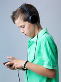Boy playing game console against grey background — Stock Photo