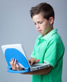 Boy with laptop on grey background — Stock Photo