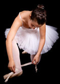 Ballerina dancer tiding up her shoe laces on black background — Stock Photo