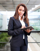 Smiling business woman using tablet PC at the office — Stock Photo