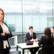 Beautiful businesswoman smiling with his colleagues behind — Stock Photo