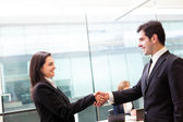 Business handshake at modern office with bussiness on bac — Stock Photo
