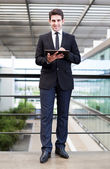 Smiling young businessman using his digital tablet at the office — Stockfoto