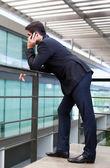 Hübscher junger Geschäftsmann auf das Bürogebäude am Telefon — Stockfoto