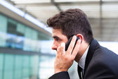 Closeup portrait of handsome business man using cell phone at th — Stock Photo