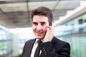 Closeup retrato de la sonriente joven empresario mediante teléfono celular — Foto de Stock