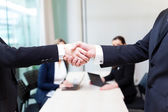 Business shaking hands in the office, finishing a meeting — Stock Photo