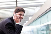 Closeup portrait of handsome business man using cell phone at th — Zdjęcie stockowe