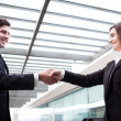 Handshake between business at modern office - Stock Photo
