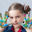 Beautiful little girl showing painted hands over grey background — Stock Photo