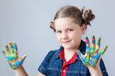 Hermosa niña mostrando pintadas las manos sobre fondo gris — Foto de Stock