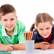 Stock Photo: Two children draw with colorful crayons and smile, isolated over