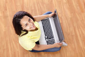 Young happy smiling woman with laptop working at home — Stok fotoğraf