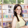 Portrait of pretty girl looking at camera in college library  — Stock Photo